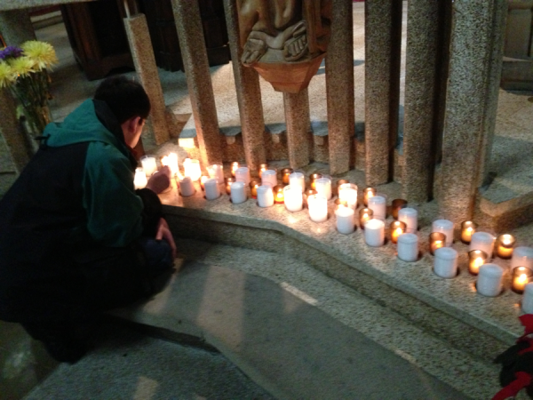 James Miller-Marquez lighting candles for Harry Miller at the Cathedral in Columbus.